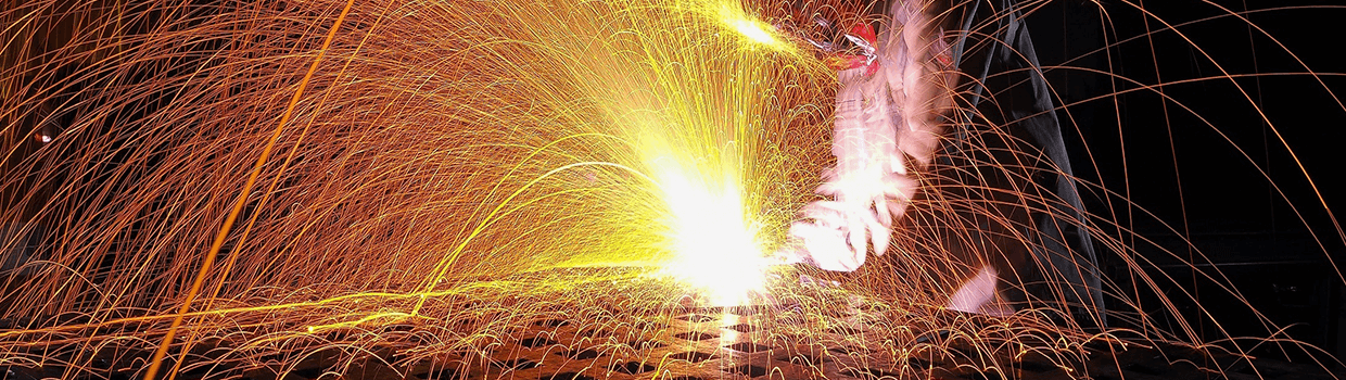 Sparks shooting up from a welder working on a flat metal structure