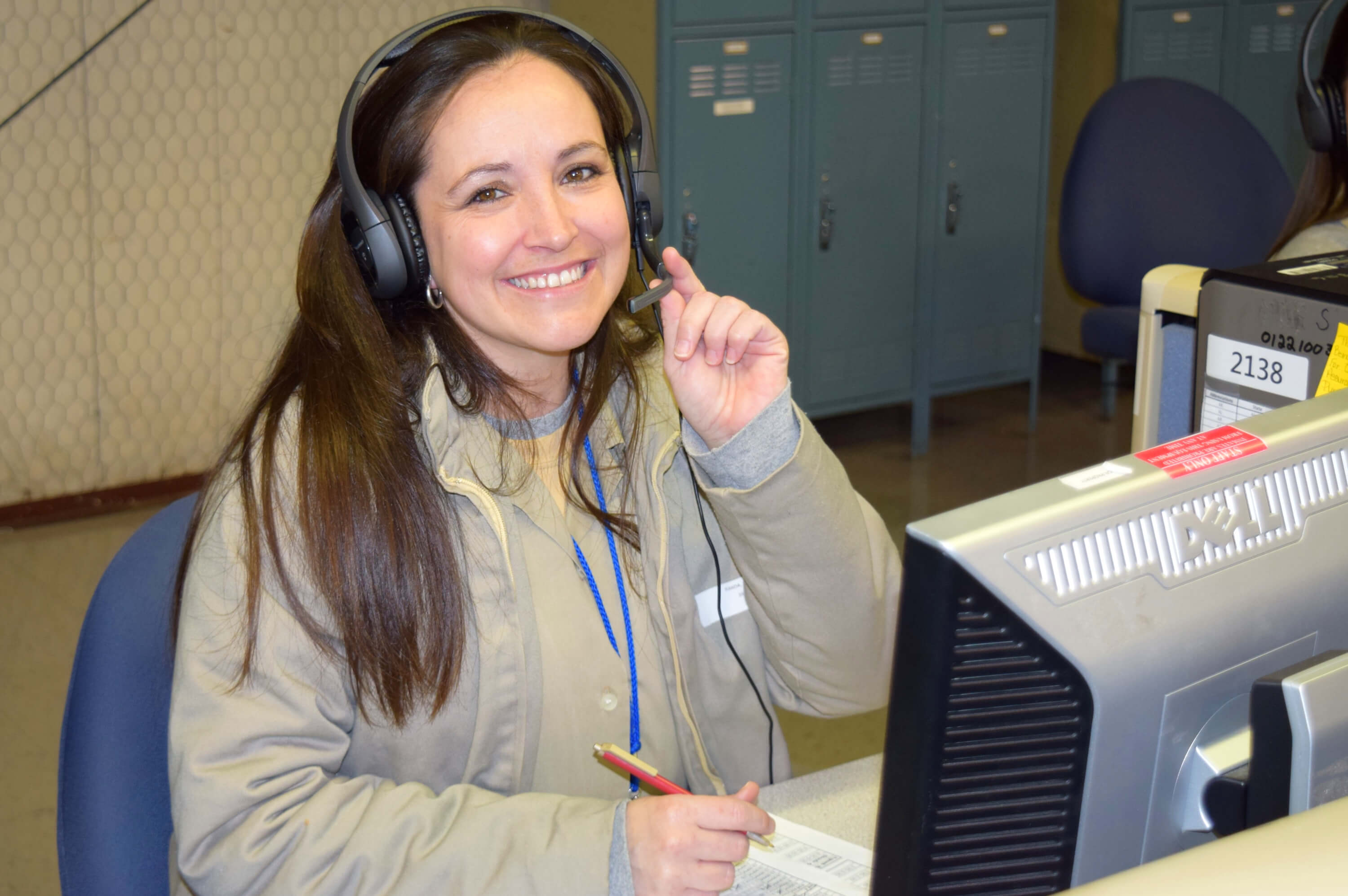 A UNICOR worker smiles at the camera as she works at a contact center terminal