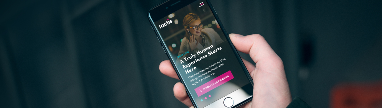 An iPhone being held in a hand showing the Tactis homepage
